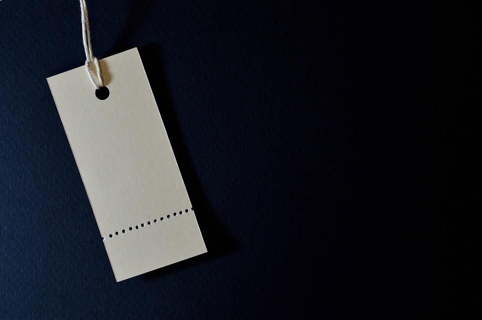 Prisskilt af papir hænger i snor foran mørk baggrund
